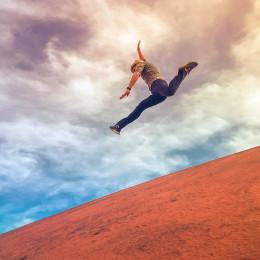 Man Jumping Down A Hill